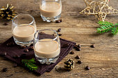 Irish cream coffee liqueur with Christmas decoration and ornaments over rustic wooden background - festive Christmas alcoholic drink