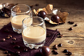 Irish cream coffee liqueur with ice, chocolate candies and coffee beans over rustic wooden background - homemade festive alcoholic drink