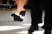 Legs of male and female irish dancers in hard shoes (stepping shoes).