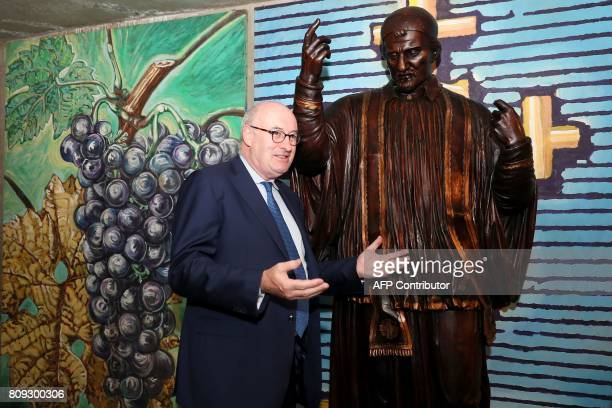 Irish European Commissioner for Agriculture and Rural Development Phil Hogan gestures as he poses beside a statue of Bacchus during his visit to...