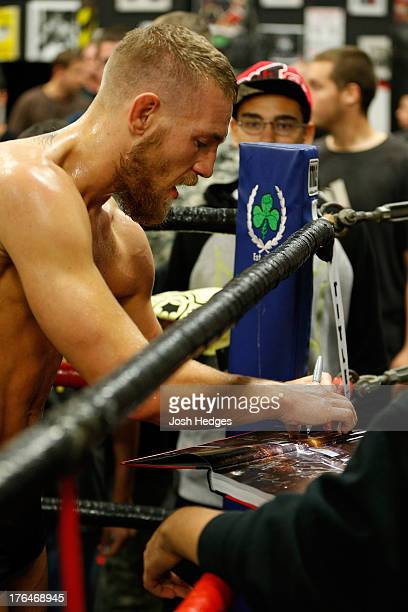 Irish featherweight Conor McGregor signs autographs for fans during an open training session for media at Peter Welch's Boxing Gym on August 13 2013...