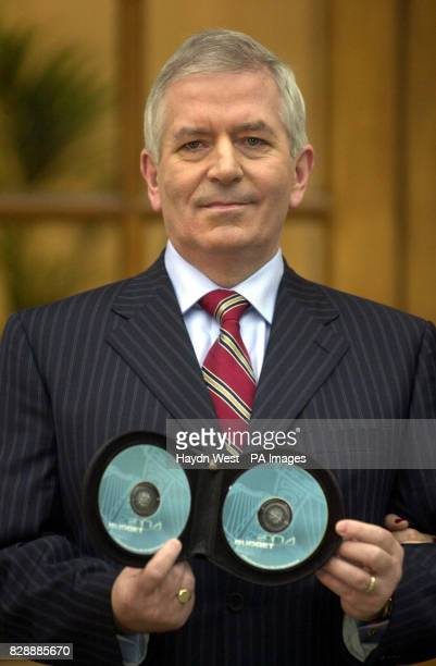 Irish Finance Minister Charlie McCreevy outside Government Buildings in Dublin Ireland with two CDs containing the Irish Budget Schools and roads are...