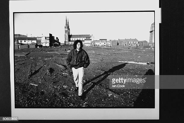 Irish folk hero Gerry Conlon standing on muddy vacant field where Divis Flats a famous trouble area used to stand as church bldgs loom in the bkgd he...