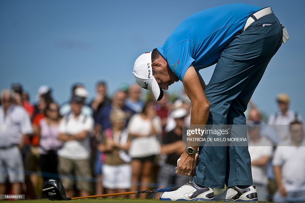 Irish golfer Simon Thornton ties up his shoe laces during the last day of the Portugal Masters golf tounament at Victoria Golf Course in Vilamoura, southern Portugal, on October 13, 2013.