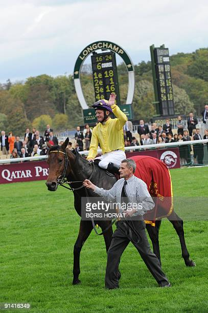 Irish jockey Mickael Kinane on 'Sea the Stars' waves after winning the 88th edition of the Arc de Triomphe prize at the Longchamp racecourse in Paris...