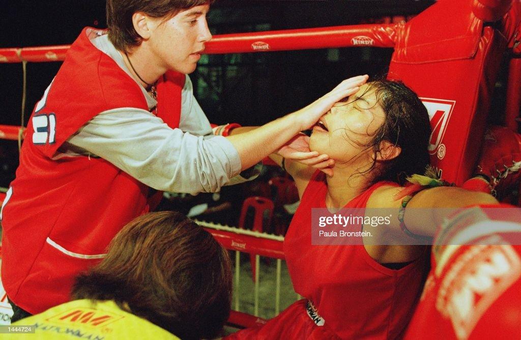 Irish kick boxer Niamh acts as 'corner man' giving the water and needed care between bouts to Muay Thai kick boxer Boonterm May, 2000 at Rangsit stadium in Bangkok, Thailand.