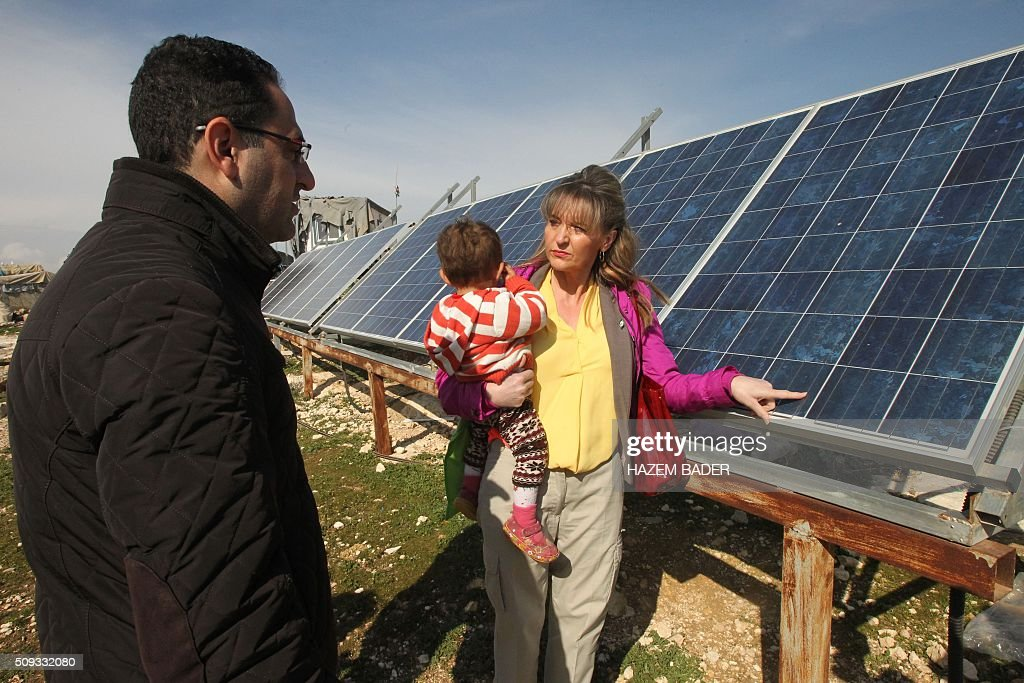 Irish Martina Anderson (C), a member of the European Parliament, holds a Palestinian baby as she stands in front of solar panels donated by the European Union during a visit by European MPs to the Palestinian village of Susya, south-east of Hebron, in the Israeli-occupied West Bank, on February 10, 2016. Israel's High Court ruled in May 2015 that Susya's 340 residents could be relocated and its structures demolished, which Human Rights Watch derided as 'a grave breach' of Israel's obligations to the Palestinian populace under its military rule. / AFP / HAZEM BADER