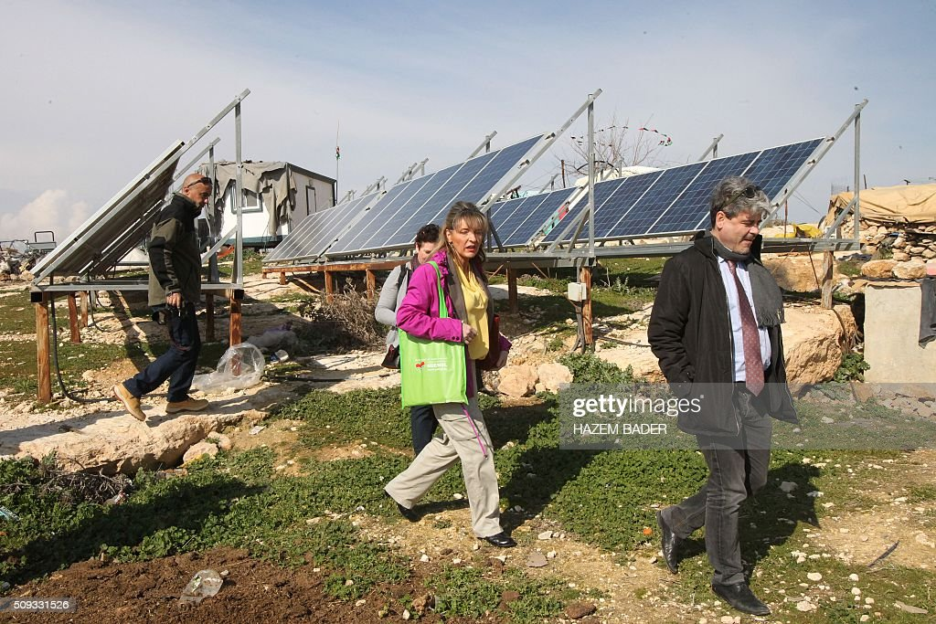Irish Martina Anderson (C), a member of the European Parliament, walks pat solar panels donated by the European Union as she leads delegation of MPs during a visit to the Palestinian village of Susya, south-east of Hebron, in the Israeli-occupied West Bank, on February 10, 2016. Israel's High Court ruled in May 2015 that Susya's 340 residents could be relocated and its structures demolished, which Human Rights Watch derided as 'a grave breach' of Israel's obligations to the Palestinian populace under its military rule. / AFP / HAZEM BADER