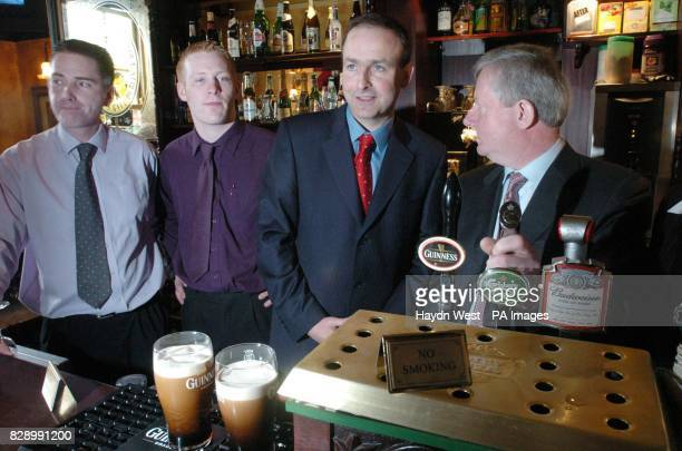 Irish Minister for Health and Children Michael Martin and manager of Maguire's pub Ted O'Sullivan and his barstaff pose during a photocall at...