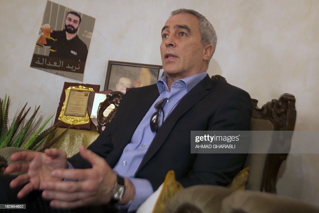 Irish MP Pat Sheehan sits in the Issawi home on March 2, 2013 in the Arab east Jerusalem neighbourhood of Issawiya next to a poster of Samer Issawi, a Palestinian held in Israeli jail and on hunger strike for more than 200 days. Sheehan, who participated in the 1981 hunger strike in British prisons for 55 days, was part of a delegation of European politicians from the Council for European Palestinian relations who paid a solidarity visit to Issawi's family on March 2, 2013.