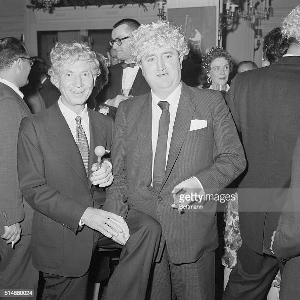 Irish playwright Brendan Behan wearing a wig clowns with Harpo Marx at a party