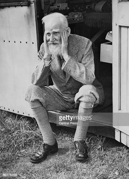 Irish playwright George Bernard Shaw sits in the doorway of the garden shed at his home in Ayot St Lawrence Hertfordshire where he does most of his...
