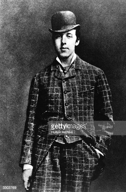 Irish playwright novelist and wit Oscar Wilde wearing a checked threepiece suit and bowler hat