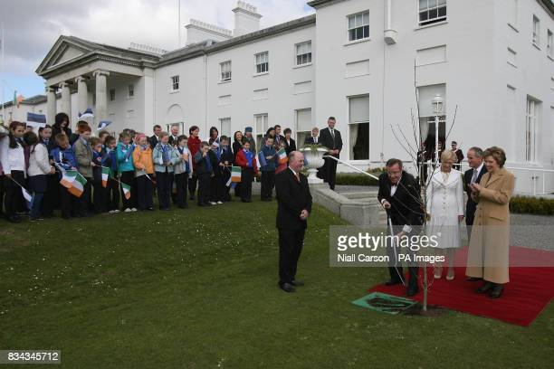 Irish President Mary McAleese right claps as the President of Estonia Toomas Hendrik Ilves centre plants a tree at Aras an Uachtarain as he begins a...