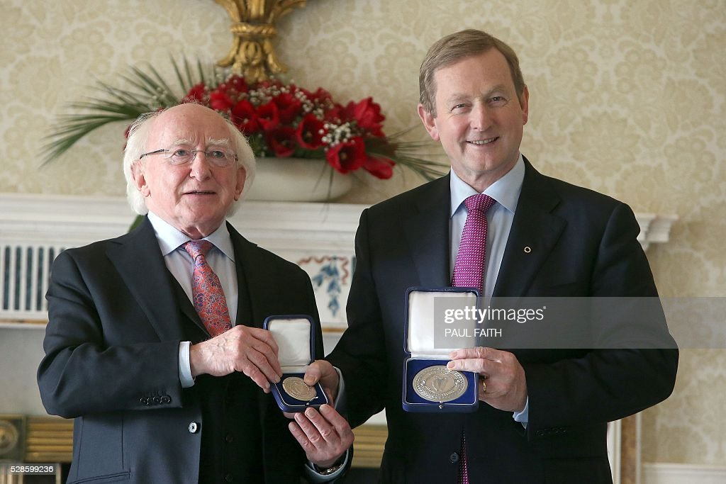 Irish President Michael D Higgins (L) poses for pictures in Dublin, Ireland, on May 6, 2016, with re-elected Irish Prime Minister Enda Kenny, after Higgins signed the 'Warrant of Appointment' and Kenny was officially re-appointed as Prime Minister for a second term. Ireland's parliament re-elected Enda Kenny as prime minister at the head of a minority government on Friday following a deal aimed at a slight easing of austerity after more than two months of impasse. / AFP / Paul Faith