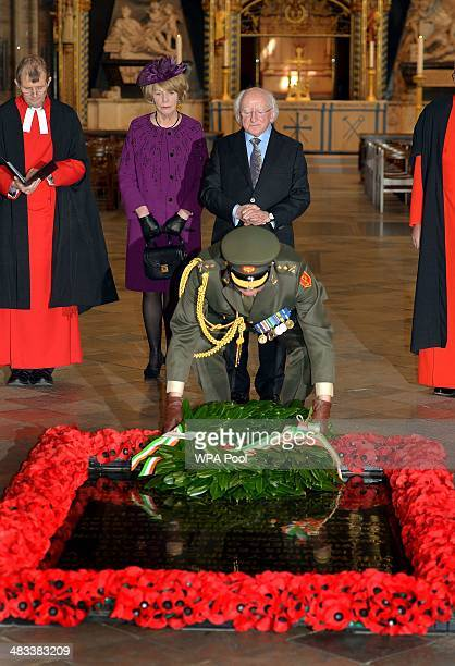 Irish President Michael D Higgins watches with his wife Sabina as an Irish solider lays a wreath at the grave of the Unknown Warrior during a visit...