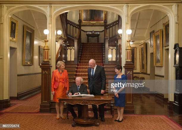 Irish President Michael Higgins and his wife Sabina signs a visitor's book with New South Wales state Governor David Hurley and his wife Linda...