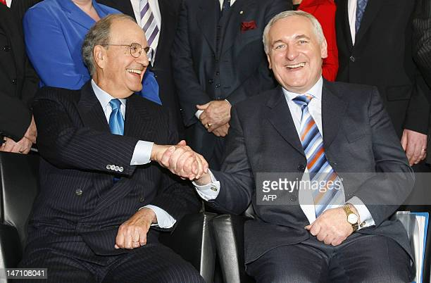 Irish Prime Minister Bertie Ahern and former US senator George Mitchell shake hands during a photocall at the BBC studios in Belfast Northern Ireland...