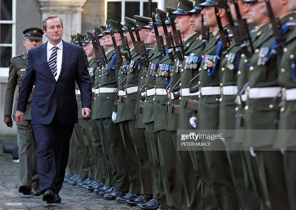 Irish Prime Minister Enda Kenndy inspects the Irish Guard of Honour during a flag-raising ceremony at Dublin Castle in Dublin, Ireland on December 31, 2012 ahead of Ireland's assumption of the rotating presidency of the European Union on Jauary 1, 2013. AFP PHOTO/ PETER MUHLY