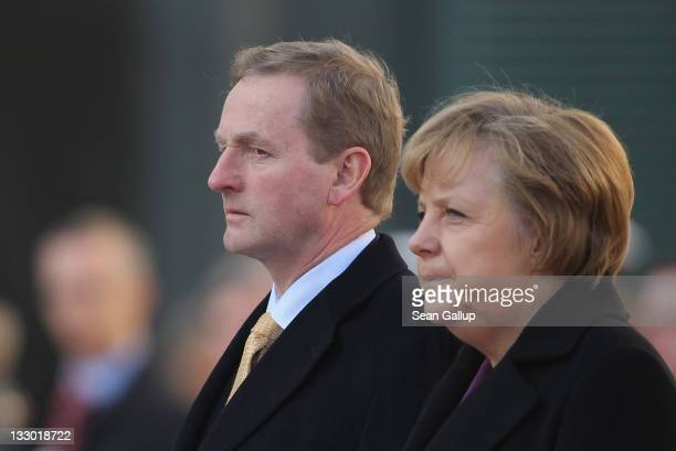Irish Prime Minister Enda Kenny and German Chancellor Angela Merkel listen to their countries' national anthems upon Kenny's arrival at the...