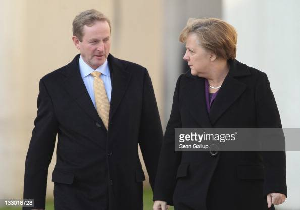Irish Prime Minister Enda Kenny and German Chancellor Angela Merkel walk toward a guard of honour upon Kenny's arrival at the Chancellery on November...