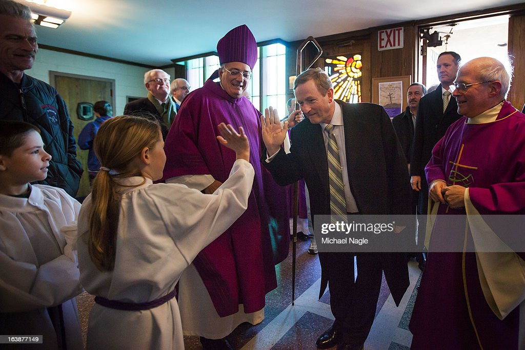 Irish Prime Minister <a gi-track='captionPersonalityLinkClicked' href=/galleries/search?phrase=Enda+Kenny&family=editorial&specificpeople=5129605 ng-click='$event.stopPropagation()'>Enda Kenny</a> (C) flanked by Rev. Nicholas DiMarzio (L), Bishop of Brooklyn, and Monsignor Michael J. Curran (right), pastor of St. Thomas More Church, hi-fives an alter girl as he arrives at St Thomas More Church for Saint Patrick's Day Mass on March 17, 2013 in the Breezy Point neighborhood in the Queens borough of New York City. Breezy Point, home to many residents with Irish ancestry, was devastated by Superstorm Sandy in October 2012.