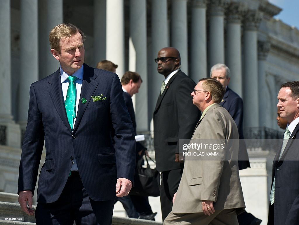 Irish Prime Minister Enda Kenny looks back at the motorcade of US President Barack Obama as he walks back to the US Capitol after the Friends of Ireland luncheon in Washington on March 19, 2013. AFP PHOTO/Nicholas KAMM
