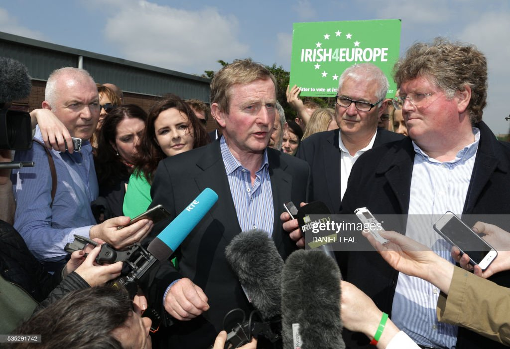 Irish Prime Minister Enda Kenny (C) speaks to members of the media during a pro-Europe event called 'Irish4Europe', before the London vs Mayo Gaelic Athletic Association (GAA) football game at Ruislip GAA grounds in Ruislip, northwest London, on May 29, 2016. Irish4Europe is a civic campaign to secure Britains future in the European Union. Enda Kenny joined activists to support the campaign and raise awareness that Irish citizens living in the UK can vote in the EU referendum on June 23, 2016. / AFP / DANIEL