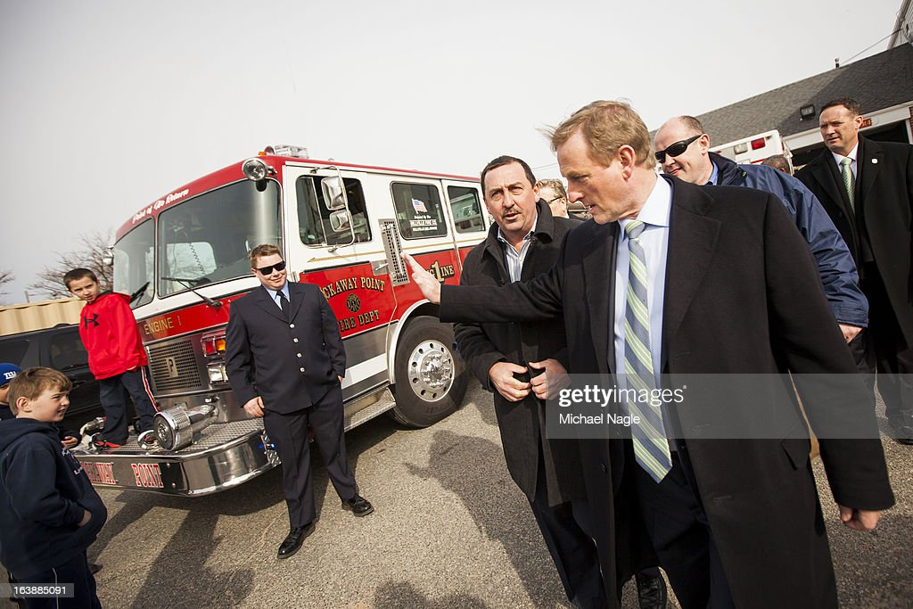 Irish Prime Minister Enda Kenny (R) waves to children playing on the front of a fire engine during a tour of the damaged Rockaway Point Volunteer Fire Department across the street from St Thomas More Church after attending Saint Patrick's Day Mass on March 17, 2013 in the Breezy Point neighborhood in the Queens borough of New York City. Breezy Point, home to many residents with Irish ancestry, was devastated by Superstorm Sandy in October 2012.