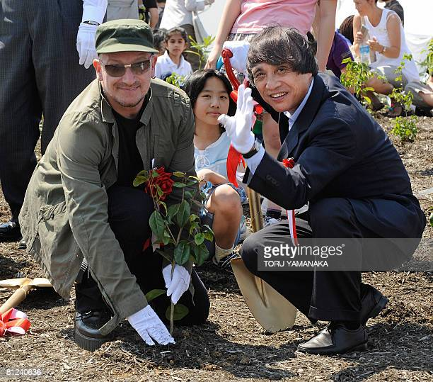 Irish rock star Bono and Japanese architect Tadao Ando plant saplings with children during a tree planting ceremony at a landfill island in Tokyo on...