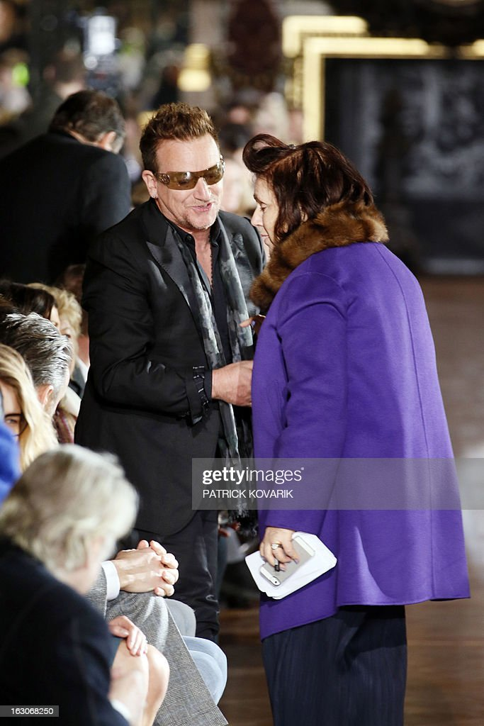 Irish singer Bono (L) shakes hands on March 4, 2013 with International Herald Tribune fashion editor Suzy Menkes as he attends Stella McCartney's Fall/Winter 2013-2014 ready-to-wear collection show in Paris.