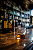 Image of a glass of whiskey on a bar with blurred background