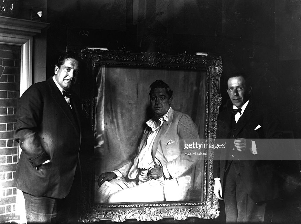 Irish-born American tenor John McCormack (1884 - 1945) with his portrait, painted by Sir William Orpen.
