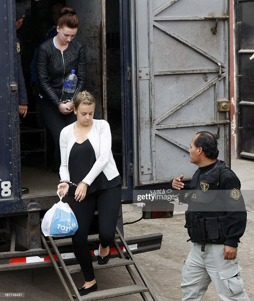 Irishwoman Michaella McCollum (back) and Briton Melissa Reid (front) disembark handcuffed from a truck in front of the Sarita Colonia Jailhouse Court in the port of Callao, west of Lima, on September 24, 2013, to appear in court on drug trafficking charges. Both women age 20 face between 15 and 18 years in jail for their alleged attempt to sneak a total of 11 kilos (24 pounds) of cocaine on a flight to Spain early August, and Reid has already indicated an intention to plead guilty in exchange for a shorter sentence, while the UK Foreign Office has confirmed there is a prisoner transfer agreement between the UK and Peru.