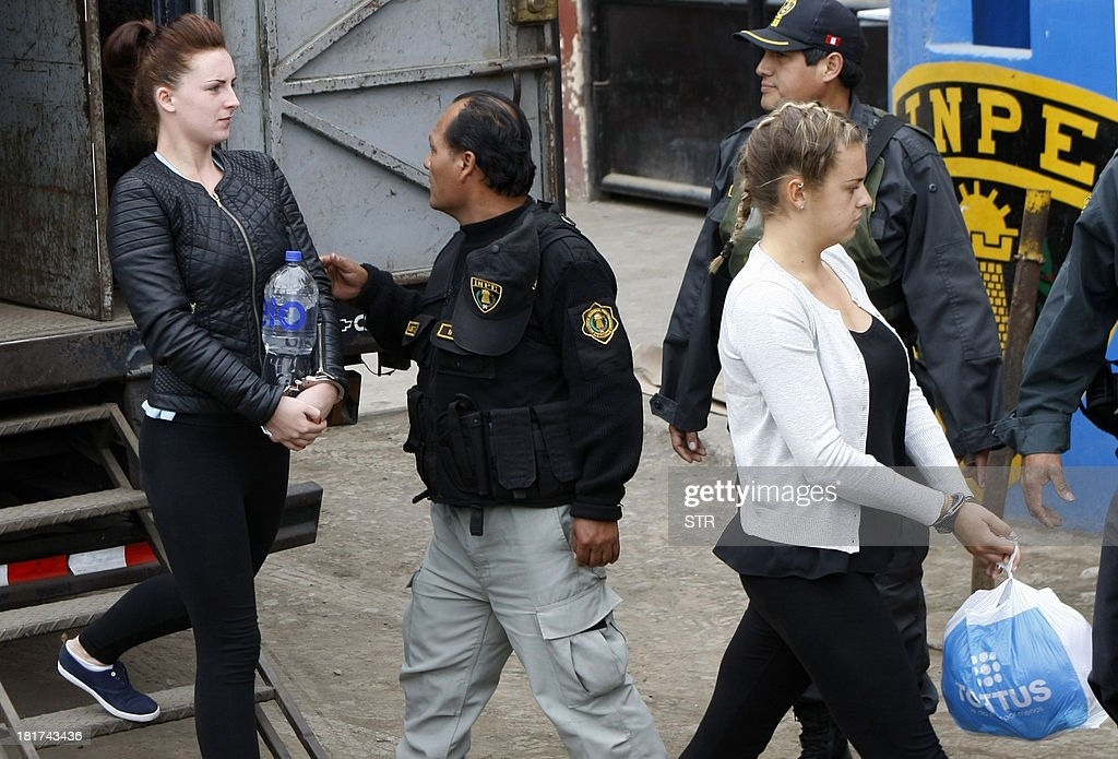 Irishwoman Michaella McCollum (L) and Briton Melissa Reid (R) walk into the Sarita Colonia Jailhouse Court in the port of Callao, west of Lima, on September 24, 2013, to appear in court on drug trafficking charges. Both women age 20 face between 15 and 18 years in jail for their alleged attempt to sneak a total of 11 kilos (24 pounds) of cocaine on a flight to Spain early August, and Reid has already indicated an intention to plead guilty in exchange for a shorter sentence, while the UK Foreign Office has confirmed there is a prisoner transfer agreement between the UK and Peru. AFP PHOTO/STR