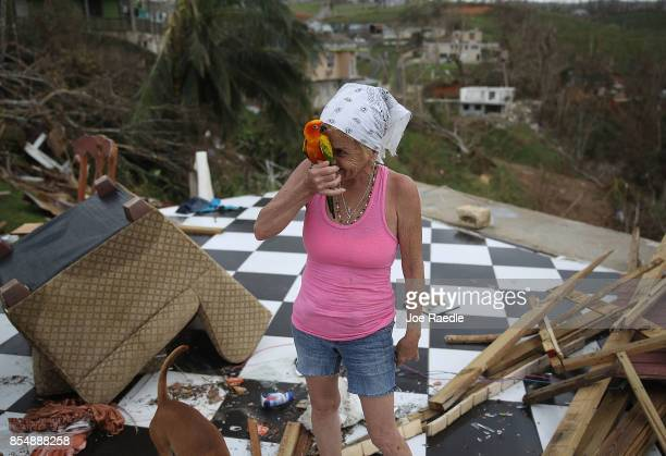 Irma Maldanado stands with Sussury her parrot in what is left of her home that was destroyed when Hurricane Maria passed through on September 27 2017...