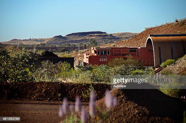 Iron ore train emerging from a load out tunnel pulled by a diesel locomotive the trains are more than two kilometres long Iron ore is currently...