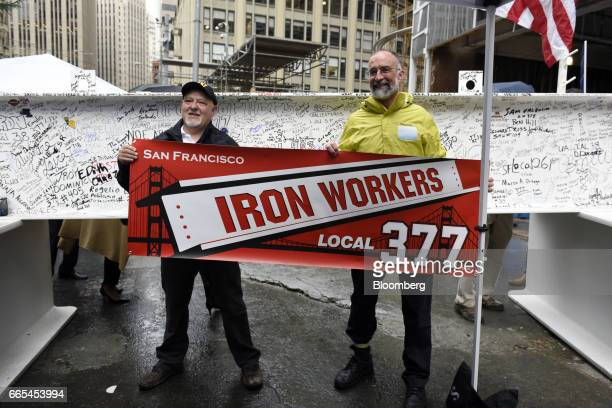 Iron workers hold a union banner while standing for a photograph in front of the final steel beam during a topping off ceremony for the Salesforce...