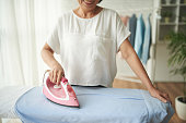 Close-up image of woman ironing clothes