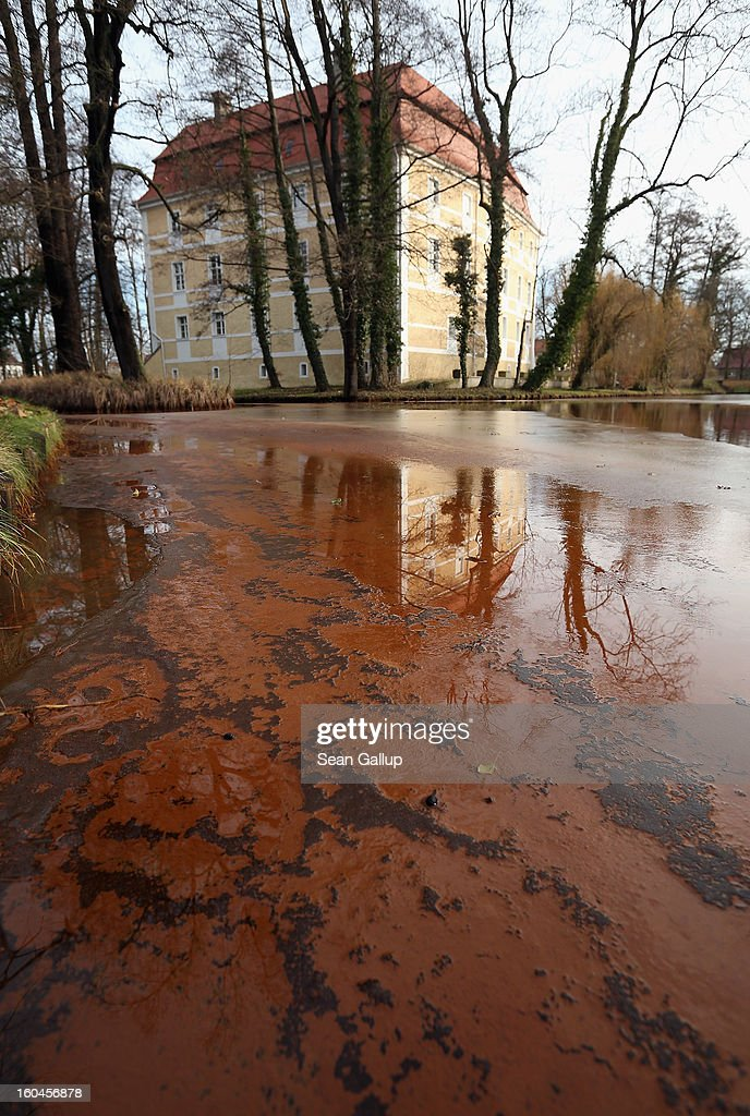 Iron-rich sludge lies on top of thawing ice in the ponds that are fed by a nearby creek next to Schloss Vetschau palace on January 31, 2013 in Vetschau, Germany. Many creeks and small Spree rivers in the regions around Vetschau and Spremberg in eastern Germany have turned a distinctive red or dark orange following the closure of nearby open-pit coal mines. Geologists say that the returning gound water levels in the former mines is bringing iron-rich ore into the water, and though the sludge isn't poisonous, environmentalists are concerned over the long-term affects.