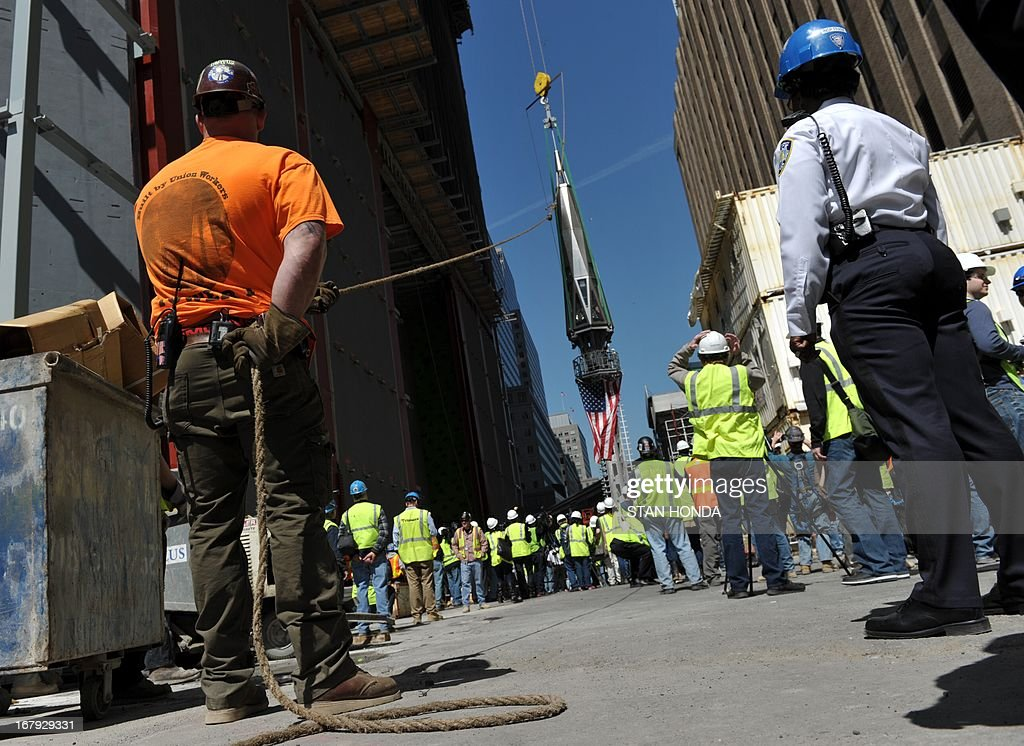 Ironworker Tommy Hickey (L) holds a rope as the final sections of the spire is raised to the top of One World Trade Center May 2, 2013 in New York to a temporary work platform atop the structure. Ironworkers will install the sections at a later date and when complete, One WTC will stand 1,776 feet (541 meters) high, making it the tallest building in the Western Hemisphere. AFP PHOTO/Stan HONDA