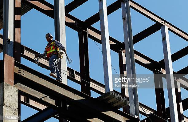 Ironworkers prepare to guide the final steel beam into place during the George W Bush Presidential Center Topping out Ceremony on October 3 2011 in...