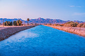 Stock photograph of an irrigation canal in Blythe, Riverside County, California USA, Colorado Desert, at twilight blue hour, with the Big Maria Mountains in the background.