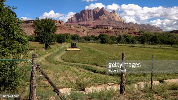 Irrigation canal pasture gate and swather cutting hay Rockville Utah