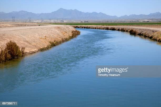 Irrigation canal thru farmland; mountains beyond