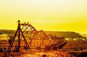 Irrigation sprinklers in rural field at sunset