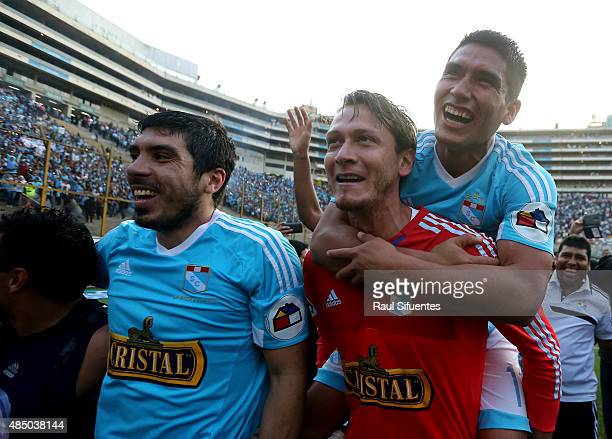 Irven Avila Mathias Martinez and Diego Penny of Sporting Cristal celebrate after winning a match between Universitario and Sporting Cristal as part...