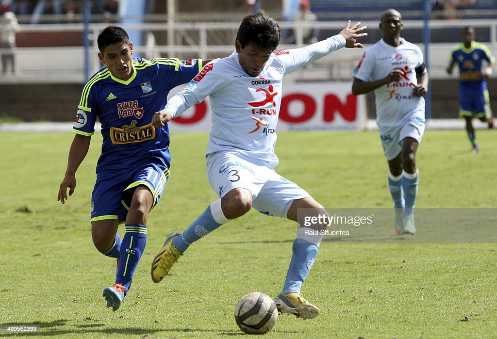 Irven Avila (L) of Sporting Cristal struggles for the ball with Jaime Huerta (R) of Real Garcilaso during a match between Real Garcilaso and Sporting Cristal as part of the Copa Inca at Municipal de Urcos Stadium on Februay 15, 2014 in Cuzco, Peru.