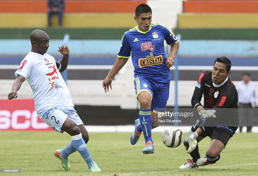 Irven Avila (C) of Sporting Cristal struggles for the ball with Juan Pretell (R) of Real Garcilaso during a match between Real Garcilaso and Sporting Cristal as part of the Copa Inca at Municipal de Urcos Stadium on Februay 15, 2014 in Cuzco, Peru.