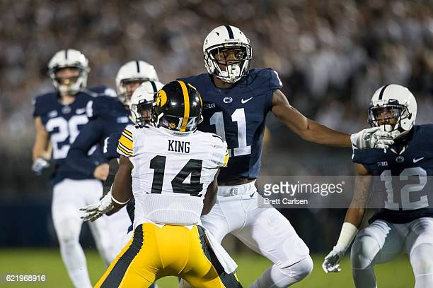 Irvin Charles of the Penn State Nittany Lions makes contact with Desmond King of the Iowa Hawkeyes and is penalized during a kicking play in the...